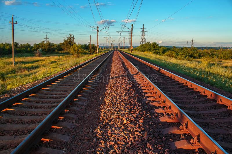 Endless railroad at the sunset time. Infinite railroad leading to infinity. A sunset landscape. A double endless railroad. Infinite railroad leading to infinity stock photo