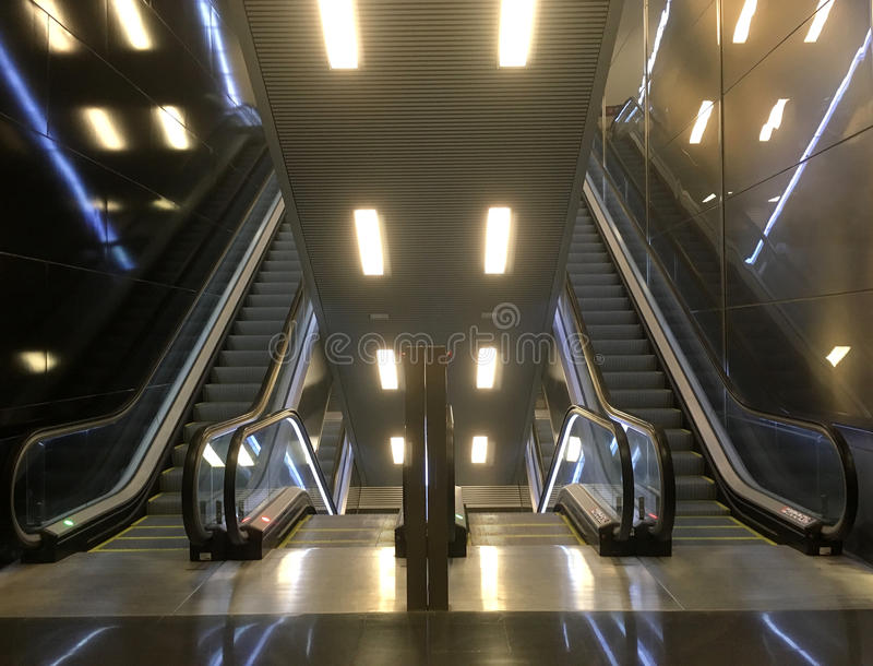 Double Escalator Ascend and Descend. A view of a double ascending and descending escalators with over head lighting at the airport in Barcelona Spain stock photography