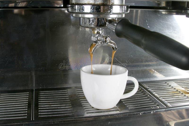 Double Espresso. Drawing a double into an espresso, americano, or cappuccino cup stock image