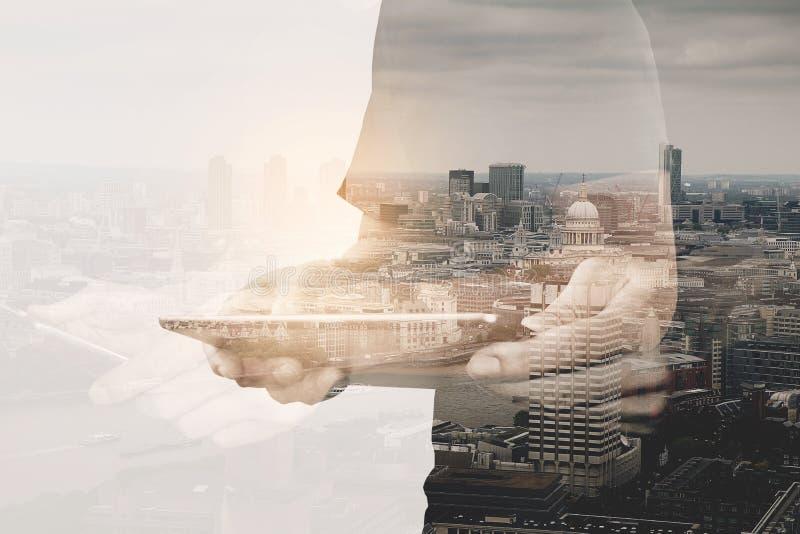 Double exposition d'homme d'affaires de succès utilisant le comprimé numérique avec photos libres de droits