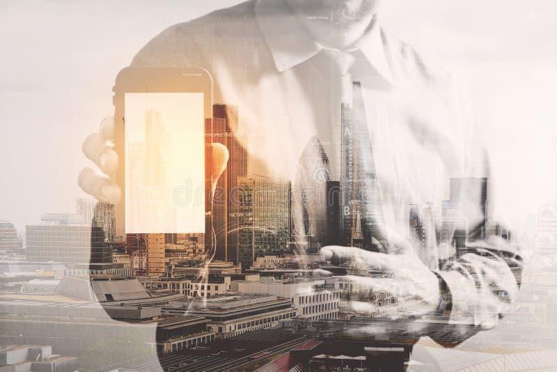 Double exposition d'homme d'affaires de succès utilisant le téléphone intelligent avec Lo images libres de droits