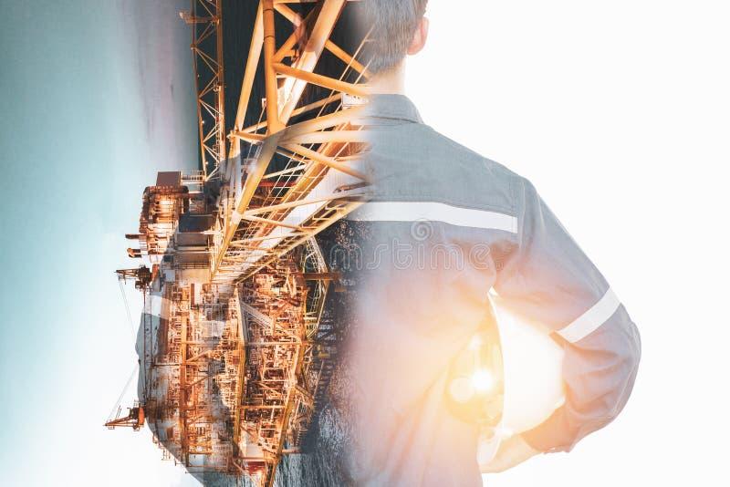 Double exposition d'homme d'ingénieur ou de technicien avec la plate-forme ou l'usine actionnée de casque de sécurité à l'aide du photo stock
