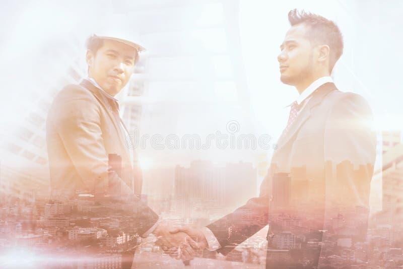 Double exposition de deux hommes d'affaires vérifiant la main photo libre de droits