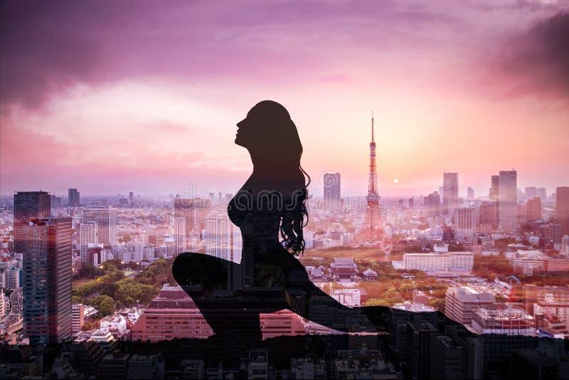 Double exposition de femme de yoga de silhouette contre la ville de Tokyo image libre de droits