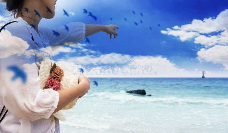 Double exposition de jeune femme de sourire dirigeant le ciel bleu de doigt photographie stock