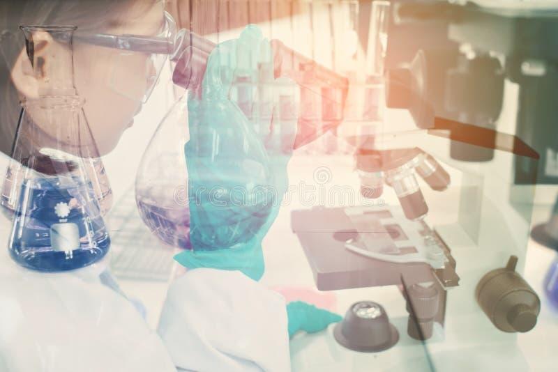 Double exposition de la fille employant l'expérience scientifique de microscope images stock