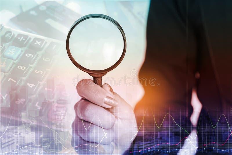 Double exposition de la main de femme d'affaires tenant la loupe avec la calculatrice de tache floue, graphique financier images libres de droits