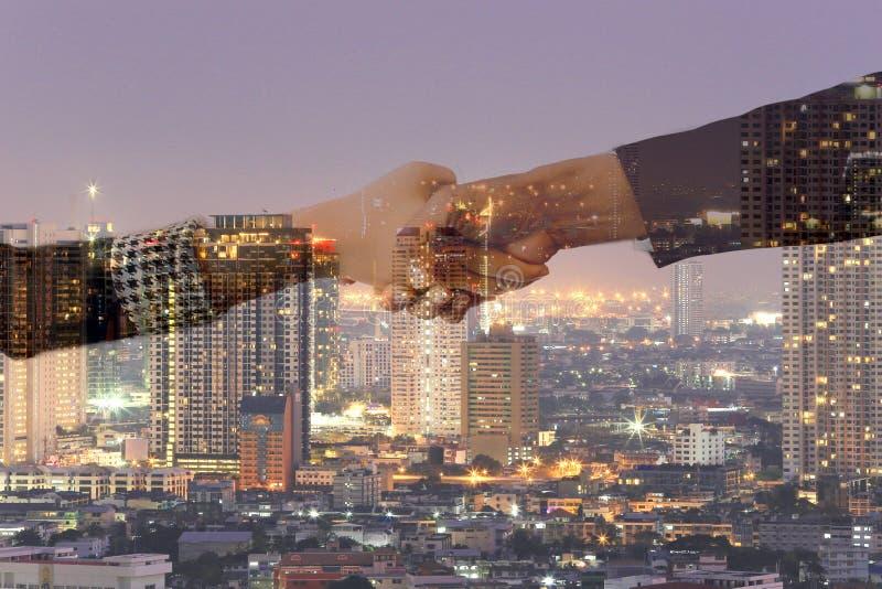 Double exposition de nuit de poignée de main et de ville images libres de droits