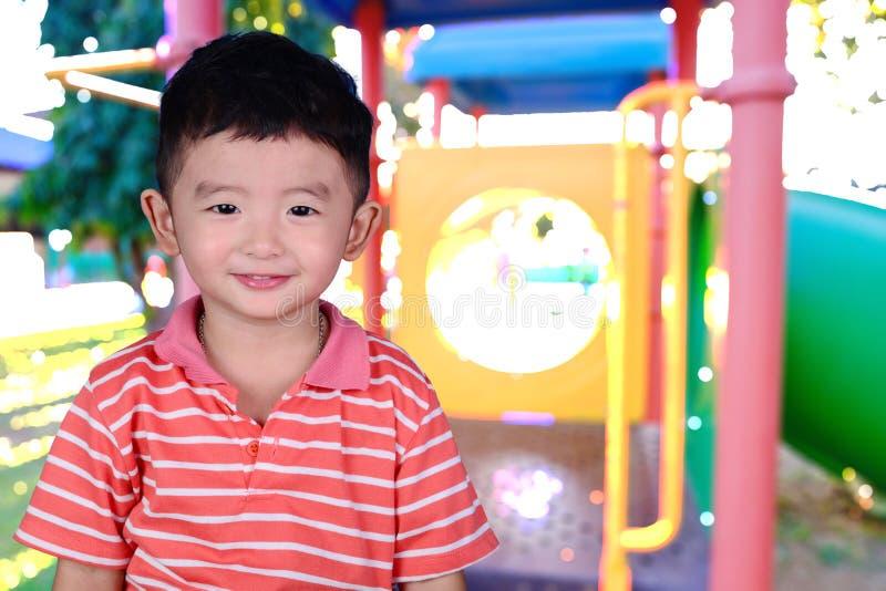 Double exposition de petit sourire heureux asiatique de garçon sur l'image de tache floue de image libre de droits