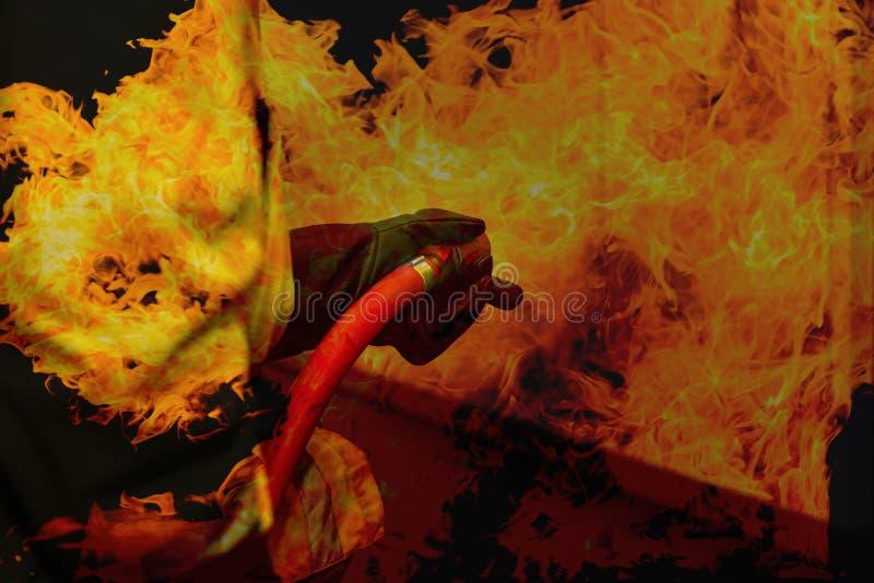 Double exposition de pompier tenant le bec à haute pression de tuyau d'incendie avec la flamme du feu de flamme photographie stock