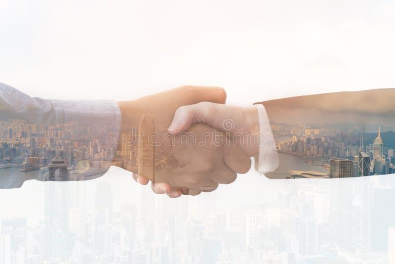 Double exposition des hommes d'affaires serrant la main sur le fond de ville photos libres de droits