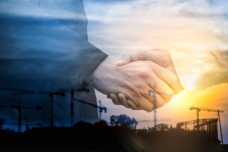 Double exposition Poignée de main d'homme d'affaires sur le fond industriel photo stock