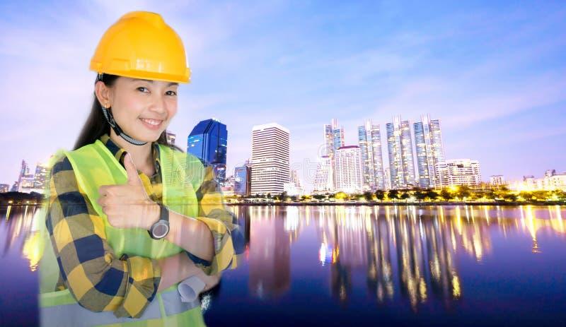 Double exposition sur des femmes machinant le casque jaune de port sur la ville de gratte-ciel photos libres de droits