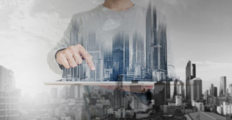 Double exposition, un homme à l'aide du comprimé numérique, et hologramme moderne de bâtiments Concept de technologie d'entrepris images stock
