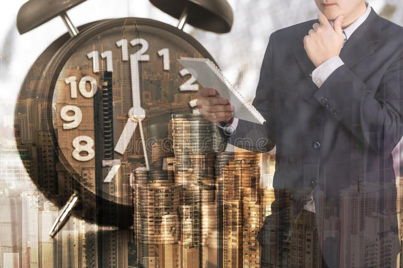 Double exposure of alarm clock and coins stacks with city background businessman and finance graph, time for savings money royalty free stock image