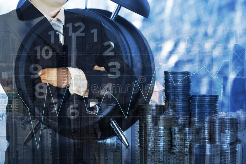 Double exposure of alarm clock and coins stacks with city background businessman and finance graph, time for savings money royalty free stock photo