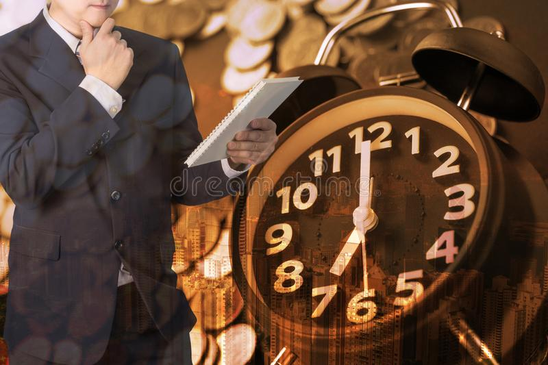 Double exposure of alarm clock and coins stacks with city background businessman and finance graph, time for savings money royalty free stock photos
