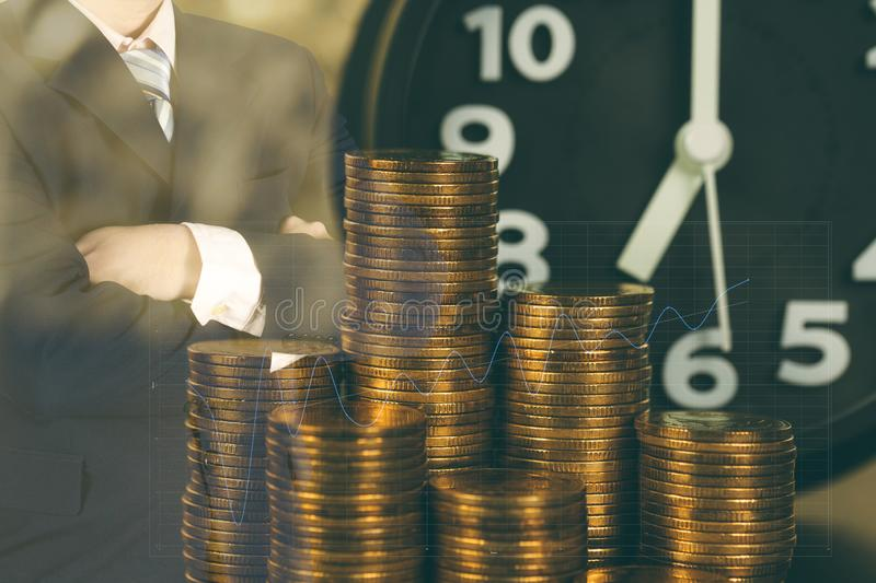 Double exposure of alarm clock and coins stacks with city background businessman and finance graph, time for savings money concept stock photography