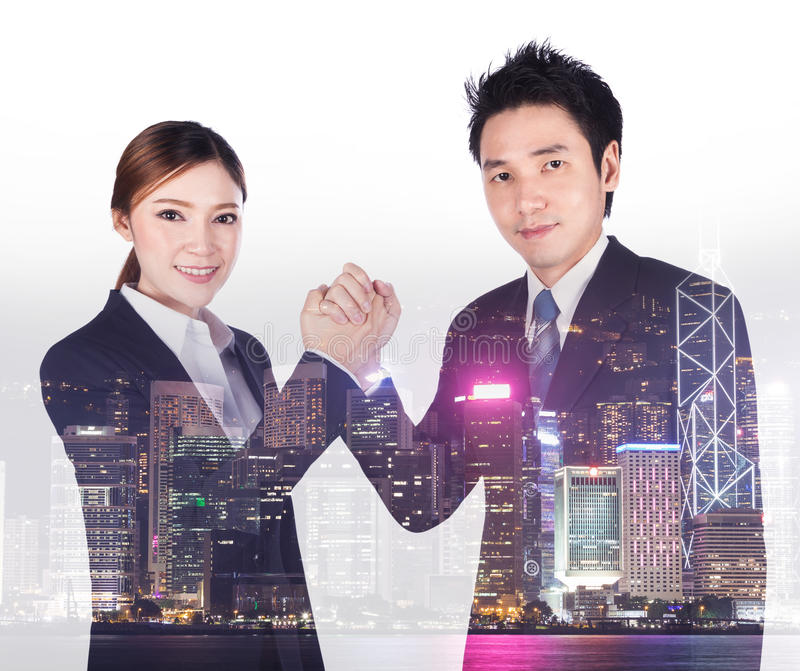 Double exposure of arm wrestling between businessman and businesswoman with city background. Double exposure of arm wrestling between businessman and stock image