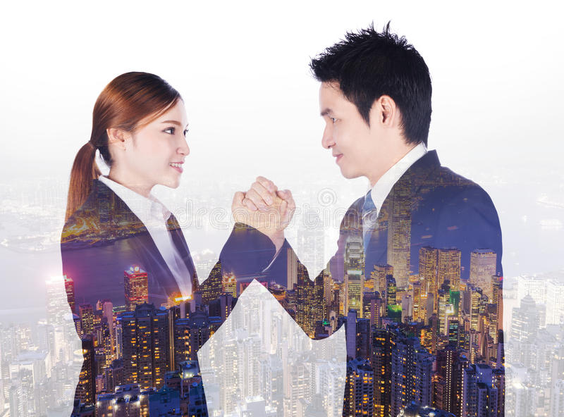 Double exposure of arm wrestling between businessman and businesswoman with city background. Double exposure of arm wrestling between businessman and royalty free stock image