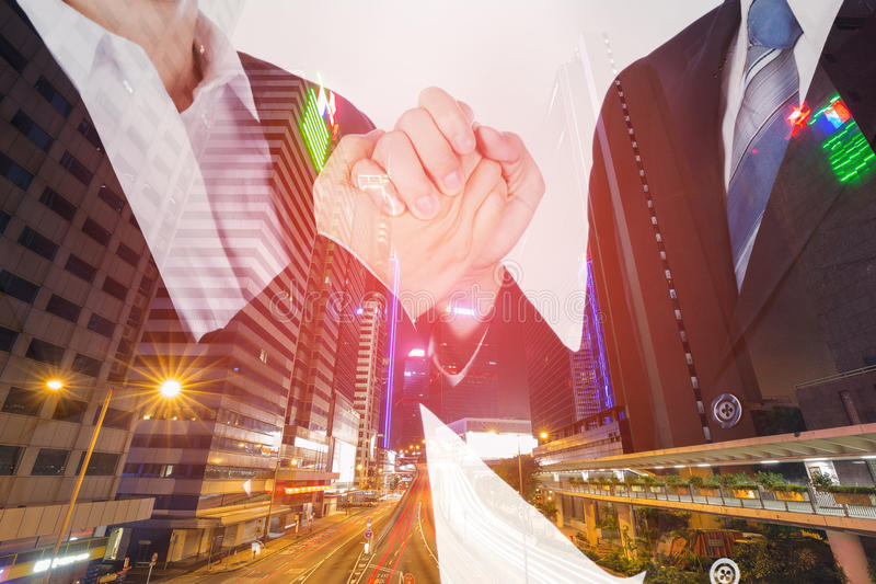 Double exposure of arm wrestling between businessman and businesswoman with city background. Double exposure of arm wrestling between businessman and royalty free stock photography