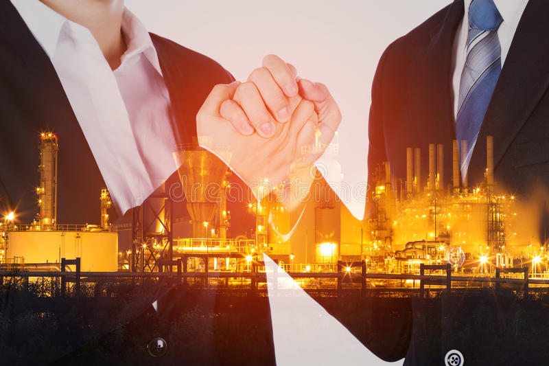 Double exposure of arm wrestling between businessman and businesswoman with oil refinery plant background. Double exposure of arm wrestling between businessman royalty free stock photos