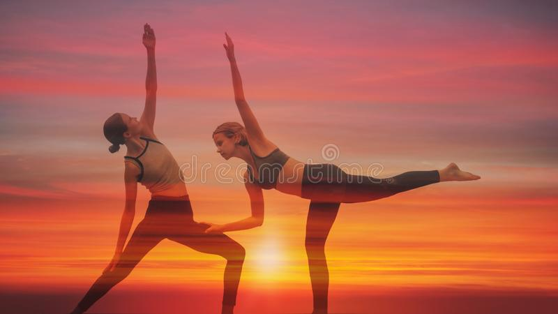 Double exposure background of two caucasian yoga partners having yoga workout posing with background of sunset sky stock photography