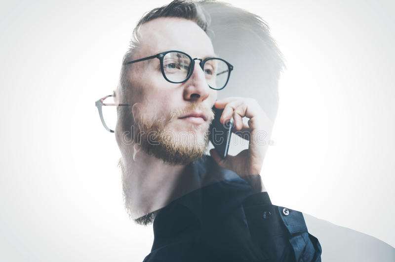 Double exposure bearded banker wearing black shirt and glasses, holding contemporary smartphone hand. Isolated white, portrait man. Background stock photos