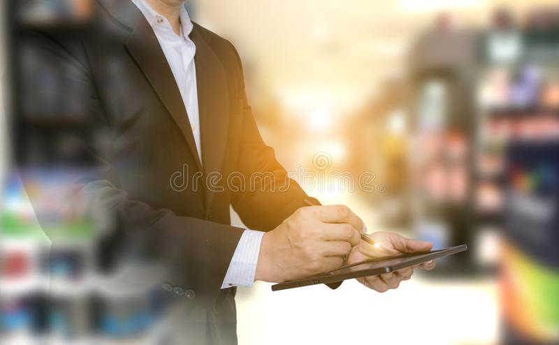 Double exposure business of checking products as hand holding the tablet. In the warehouse royalty free stock photography