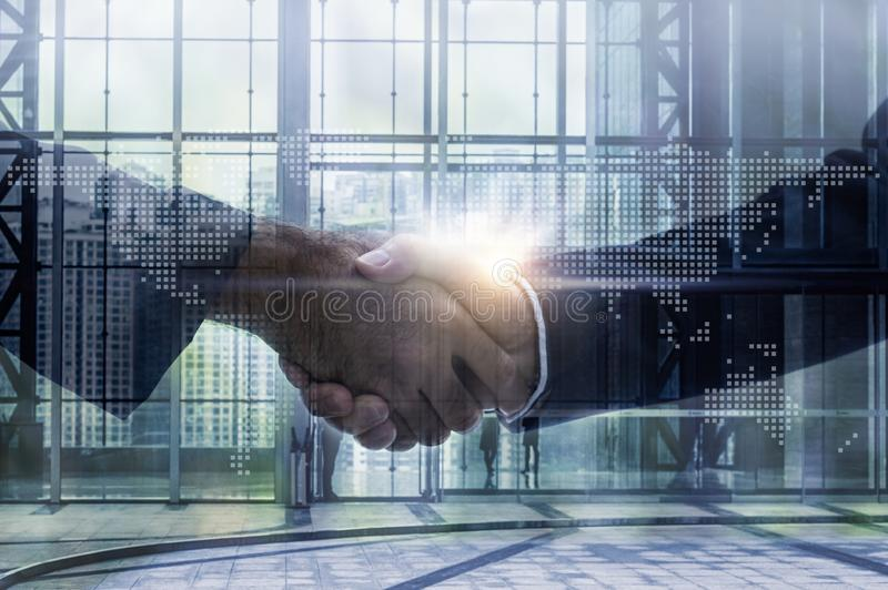 Double exposure of business handshake for successful of investment deal and city night background royalty free stock images
