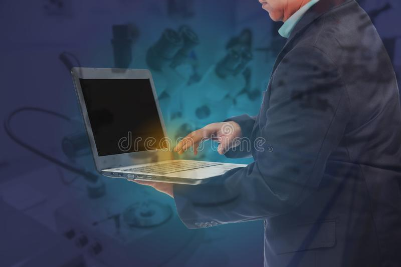 Double exposure Business man holding a laptop to work with science tool ,business. Concept stock images