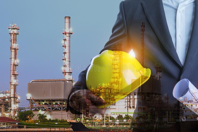 Double exposure of Business man with safety helmet and oil refinery industry plant background stock photography