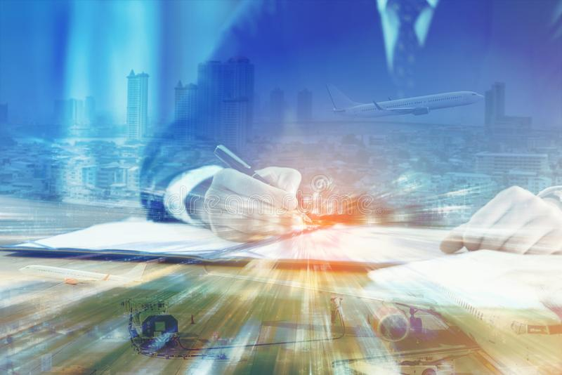 Double exposure of business man signing contract document in office with cityscape and ground crew serviced airplane. Global logistics network business stock image