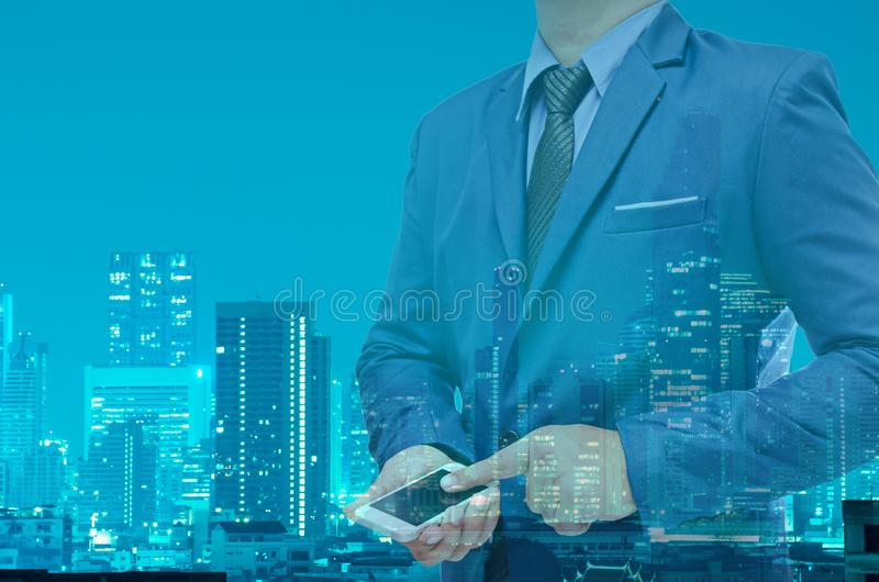 Double exposure of business man using tablet with night modern c stock photo