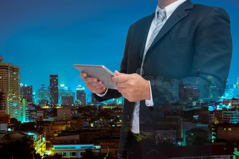 Double exposure of business man using tablet with night modern c stock image