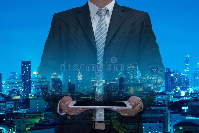 Double exposure of business man using tablet with night modern c stock photography