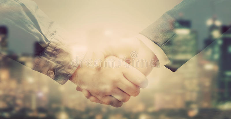 Double exposure of business people handshake on big city background. Double exposure banner of business people handshake on big city background in sunlight royalty free stock photo
