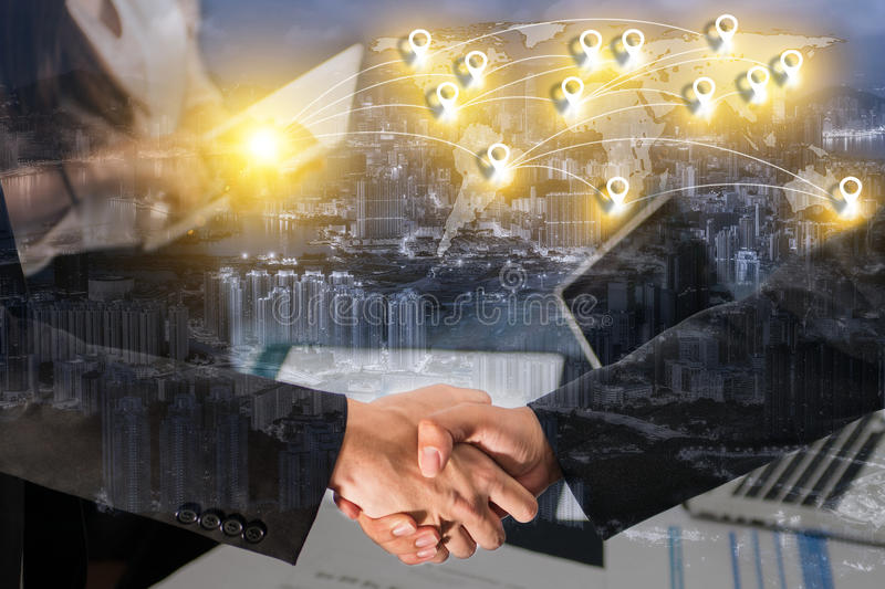 Double exposure of business people handshake greeting deal concept on blue tone of cityscape business district background with ma stock images