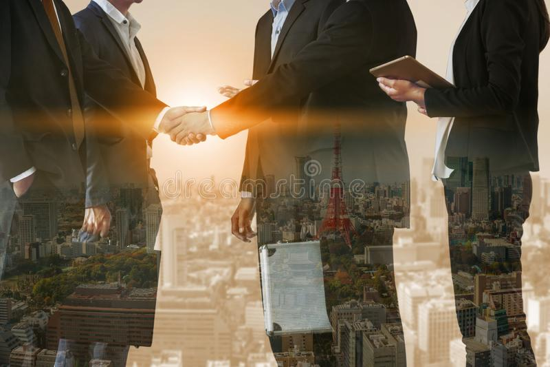 Double exposure Business People Handshake Meeting. Double exposure business people handshake agreement with cityscape in background. Business executive meeting stock photography