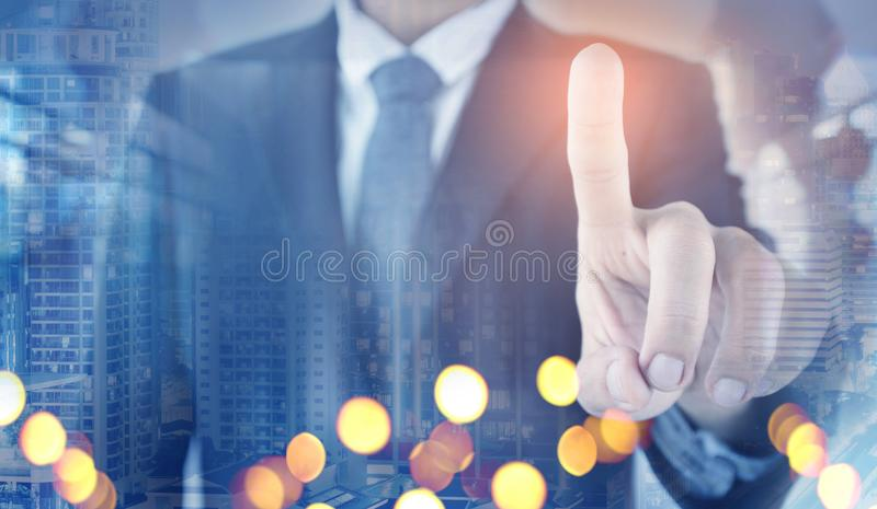 Double exposure of Business vision of Business man is pointing command blended with city night background stock image