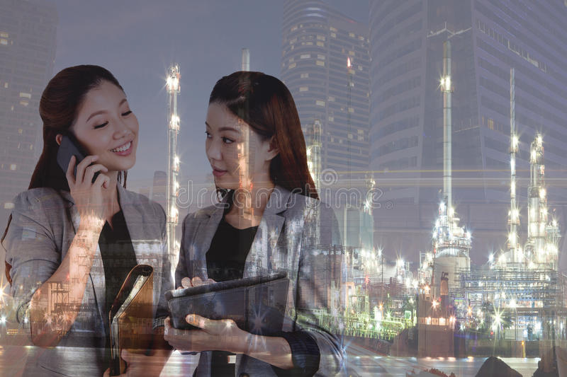 Double exposure business women/oil refinery. royalty free stock image