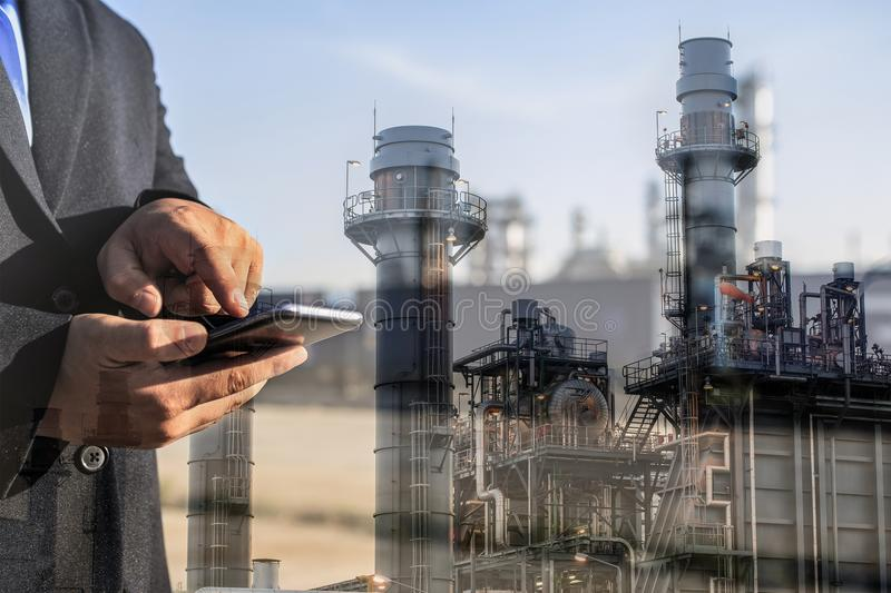 Double exposure of businessman checking oil refinery industry plant by smart phone royalty free stock photography