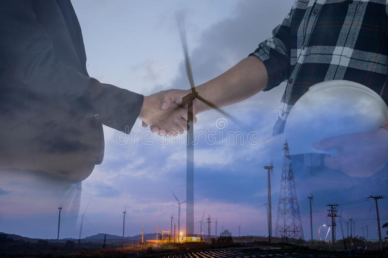 Double exposure businessman and engineer hands hake over windmill power energy. royalty free stock photos