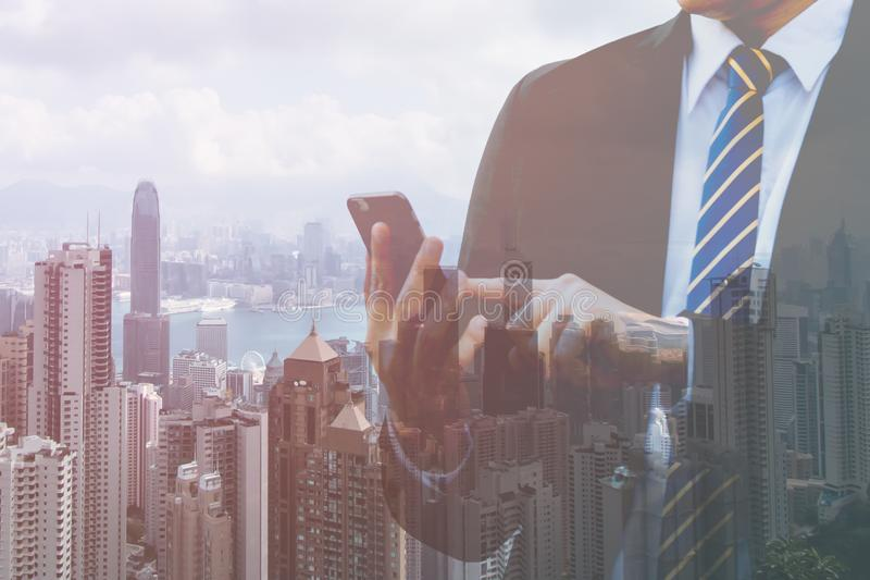 Double exposure businessman hand holding and touch screen smart phone with modern city background. Mobile, Urban, royalty free stock photos