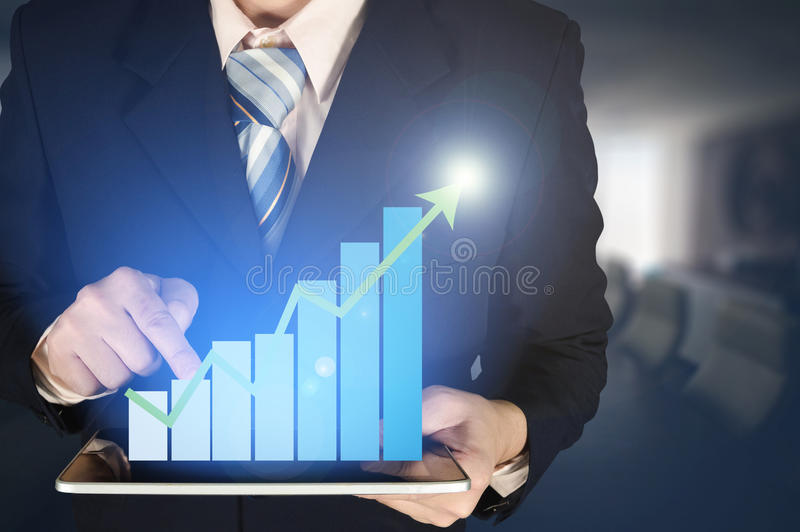Double exposure businessman hand touching virtual panel of growth bar chart on financial graph chart and blurred meeting room. Business success concept royalty free stock image
