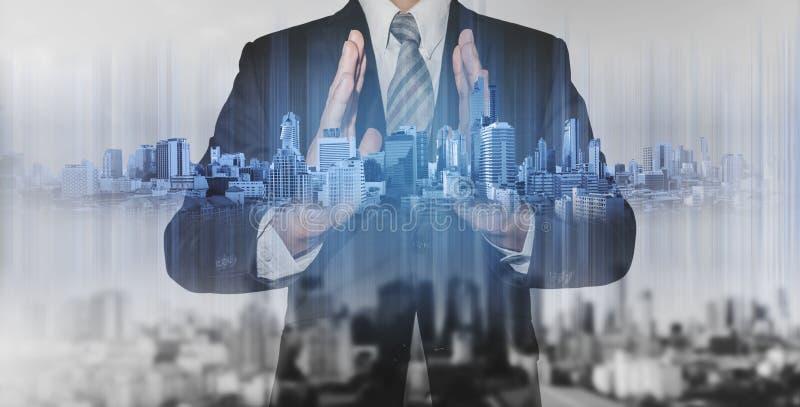 Double exposure businessman holding blue city hologram, real estate business technology. Double exposure businessman holding blue city hologram,real estate stock images