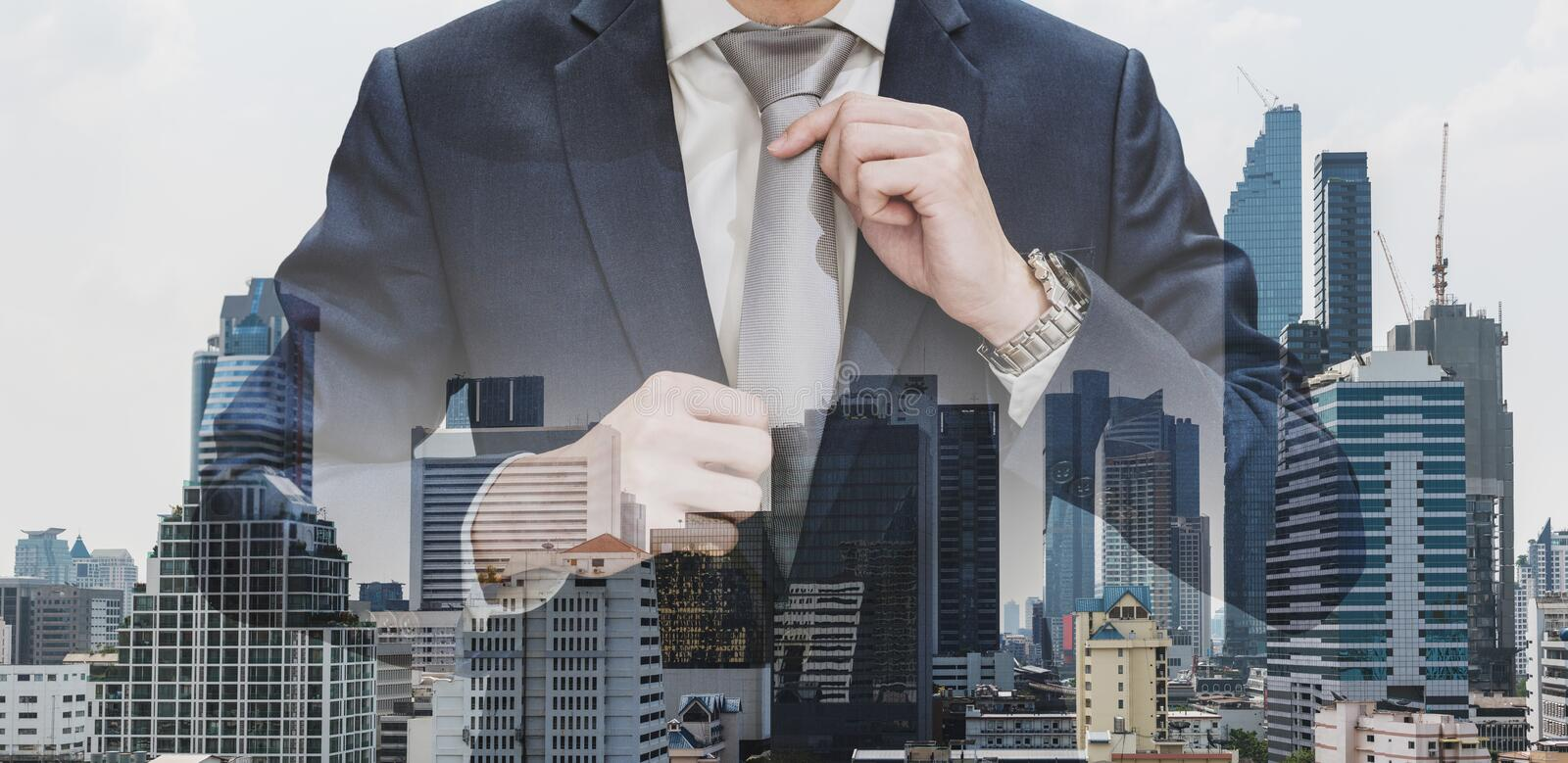 Double exposure businessman holding neck tie with modern buildings in Bangkok city background stock images