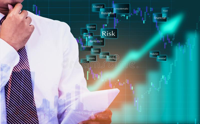 Double exposure - businessman holding a tablet in hand,The background is an arrow sign and stock graphs and icons,Concept of risk stock photography
