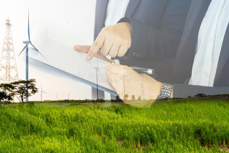Double exposure of businessman people over windmill power energy and rice field. stock photography