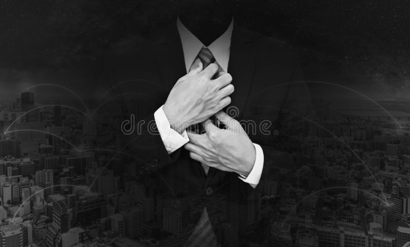 Double exposure businessman tying necktie and network in the city background. Black and white stock photo